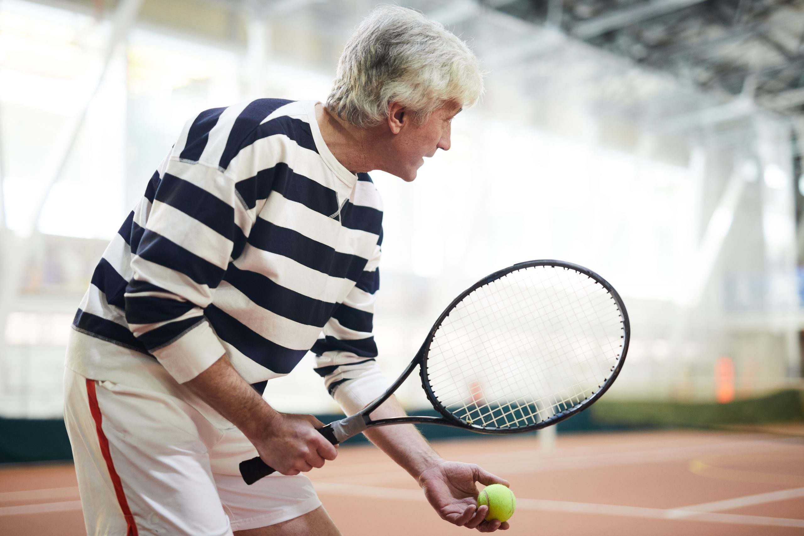 Grey-haired tennis player with racket going to throw and hit ball during game on stadium or court
