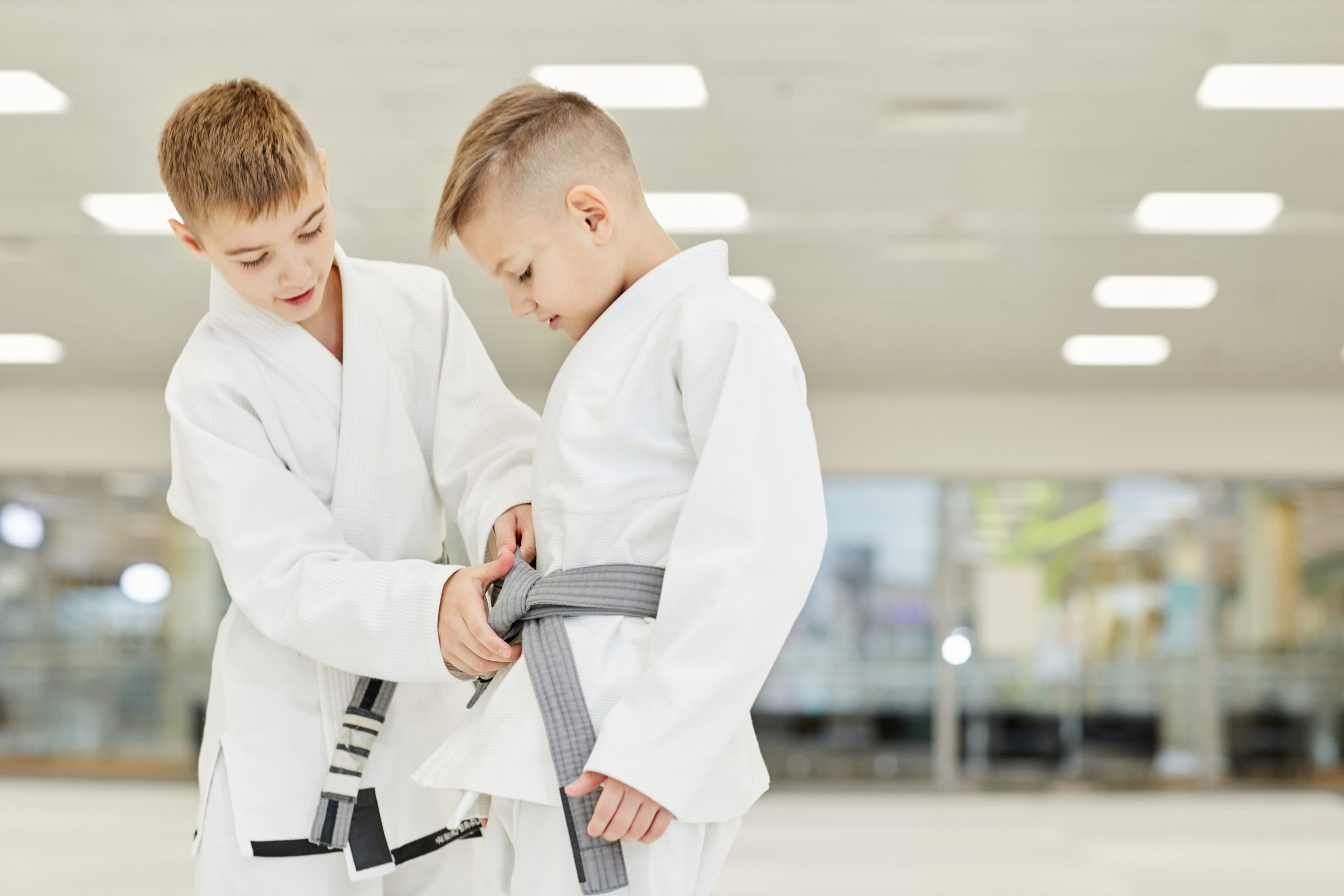 Boy in white kimono showing to his friend how to tie the belt while they standing in the gym